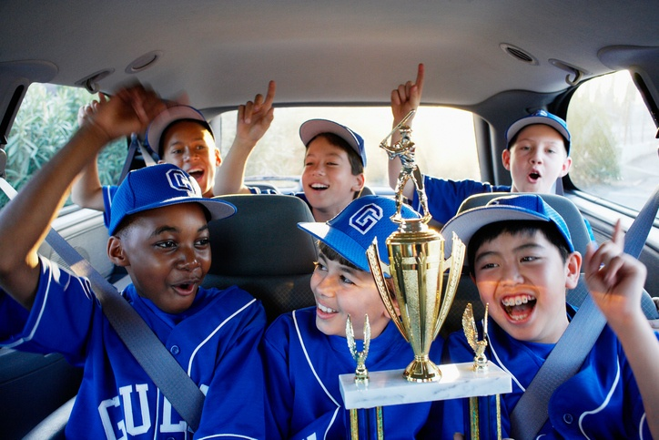boys in the car with baseball trophy