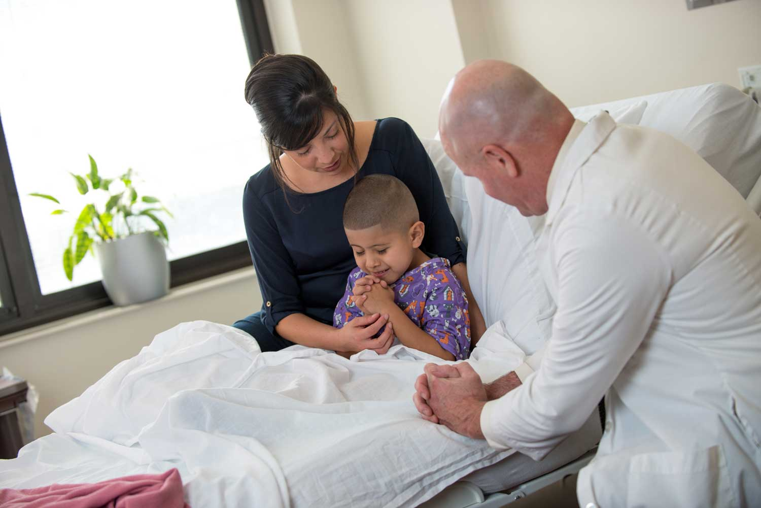doctor praying with mother and child