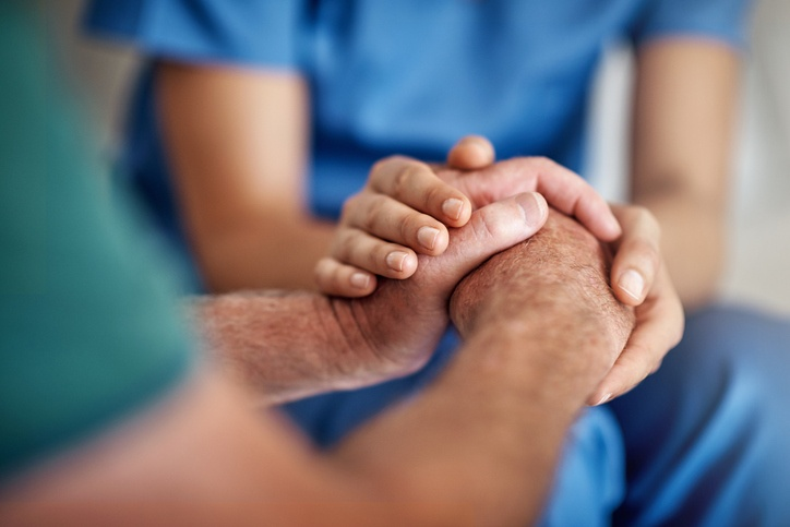 Healthcare provider holding patient's hands