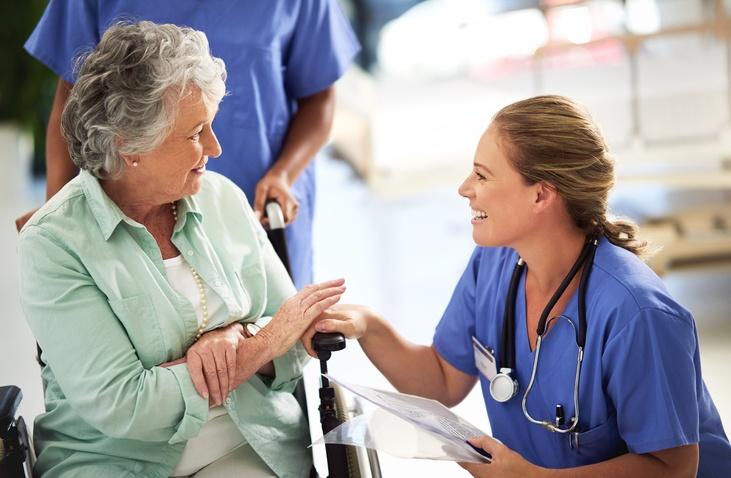 nursing talking with woman in wheelchair